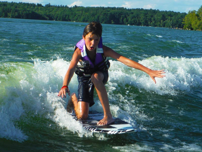 This guy's getting the hang of wake surfing really quickly. This photo was taken just before he stood for the first time, and rode his first wave without a tow rope.