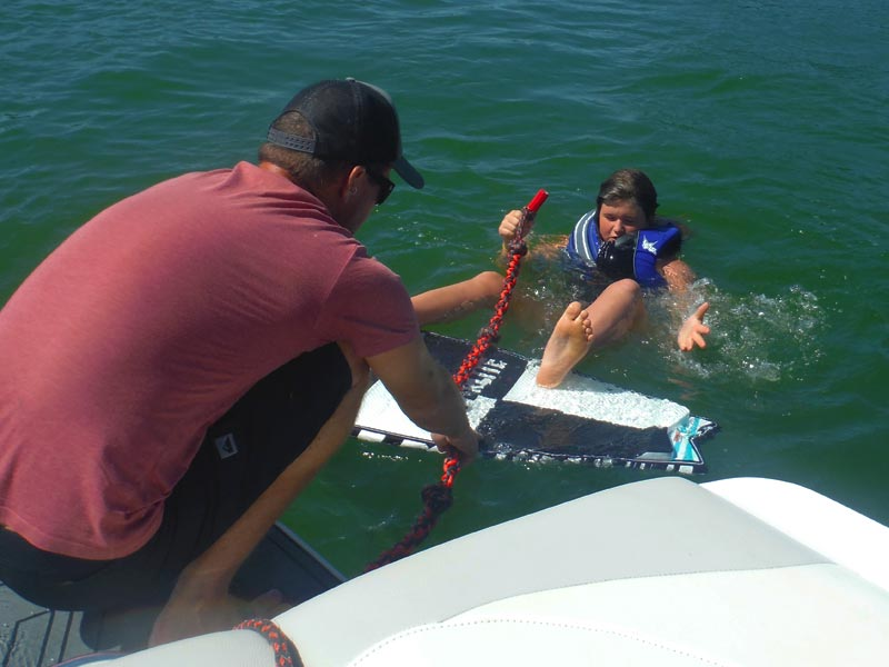 Our trusted boat captain and professional wakeboarding and wakesurfing instructor lends a helping hand to a floating camper in need of a tow rope at Mud City Summer Wake Sport Camp for Kids.