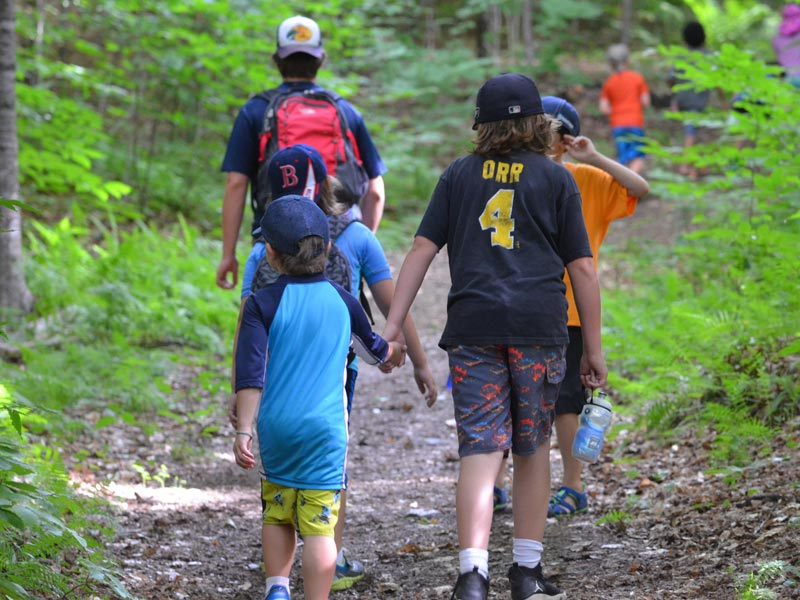Teamwork makes the dream work. Here's an older camper giving some support to a younger camper while on a hike during Mud City Adventures day camp in Stowe Vermont.