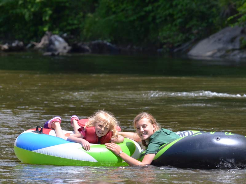 Here is a camper and a counselor having fun floating down the river in tubes. The Mud City Day Camp for kids always gets outside whenever we can.
