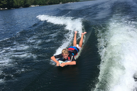 Mud City likes to have fun on our surf camp adventures. Here's a camper having a blast on while wake surfing at our summer camp for kids.